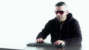 Hacker typing on computer keyboard, man in black, white background. Computer hacker, shot in RAW 4K stock video