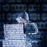 Hacker typing on a laptop Stock Photography