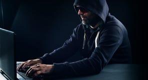 Hacker typing on laptop computer keyboard, black background Stock Image