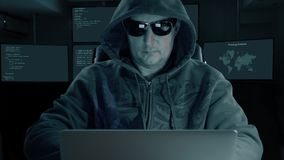 Hacker typing at laptop. Man coding on computer dark night. Man in dark glasses coughs. Front view stock video