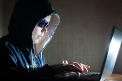 Hacker typing on a laptop Stock Photo