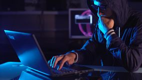 Hacker typing program code while committing a cybercrime hacking a system firewall in the dark under neon light. Hacker typing program code while committing a stock footage