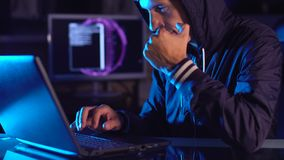 Hacker typing program code while committing a cybercrime hacking a system firewall in the dark under neon light. Hacker typing program code while committing a stock video footage