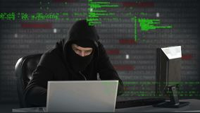 Hacker typing on two computers. Close up of a sneaky hacker wearing a balaclava and working on two computers. Th background is filled with digitally animated stock video