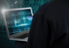 Hacker używa laptop i trzymający kredytową kartę przed cyfrowym tłem obrazy stock