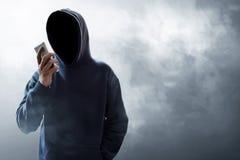 Hacker używa telefon komórkowego na dymnym tle obrazy stock