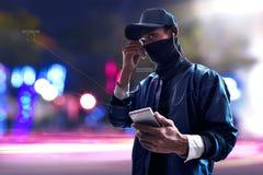 Hacker używa telefon komórkowego na ulicie zdjęcie stock