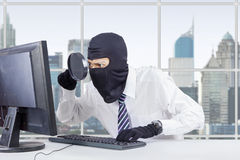 Hacker uses magnifier and mask to steal data Stock Photo