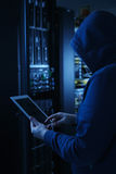 The hacker uses a tablet computer to steal information. Hooded computer hacker stealing information with Tablet PC, Server in the background Stock Photography
