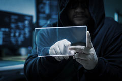 Hacker using blank clear glass tablet with blue dark and grain p Stock Photos