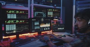 Hacker using computer with multiple monitors. Medium close-up of a young hacker using a computer with multiple monitors stock video footage