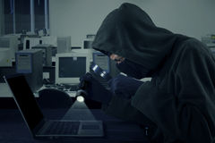 Hacker using flashlight and magnifying glass Stock Photos