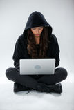 Hacker using a laptop. Against white background royalty free stock photo