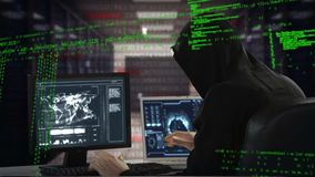 Hacker using a laptop and computer. Digital composite of Caucasian male hacker hacking into a computer with program codes moving in the screen stock footage