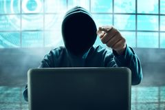 Hacker using laptop in computer room. Unknown hacker using laptop in computer room Royalty Free Stock Photo