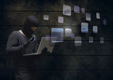 Hacker using a laptop in a dark room with digital windows. Digital composite of Hacker using a laptop in a dark room with digital windows Stock Photos