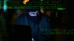 Hacker using a laptop. Digital composite of a Caucasian hacker with covered face using a laptop and program codes move in the screen stock video