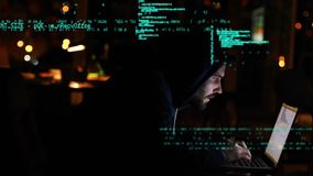 Hacker using a laptop. Digital composite of a Caucasian hacker wearing a hoodie, using a laptop while program codes move in the foreground stock footage