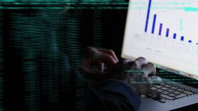 Hacker using a laptop. Digital composite of a hacker using a laptop with graphs on the screen and program codes moving in the screen stock footage