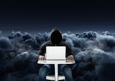 Hacker using a laptop in front of cloudy black background Royalty Free Stock Images