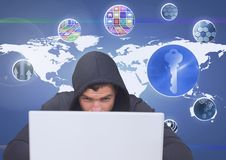 Hacker using a laptop in front of digital background with graphics ans mapworld. Digital composite of Hacker using a laptop in front of digital background with stock images