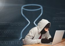 Hacker using a laptop in front of digital background with an hourglass Royalty Free Stock Photo