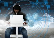 Hacker using a laptop in front of digital signs. Digital composite of Hacker using a laptop in front of digital signs Royalty Free Stock Images