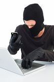 Hacker using laptop and phone Stock Photos