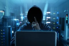 Hacker using laptop in sever room. Unknown hacker using laptop in sever room Stock Photos