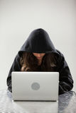 Hacker using a laptop. Hacker sitting at table and using a laptop against white background stock photo