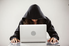 Hacker using a laptop. Hacker sitting at table and using a laptop against white background royalty free stock images