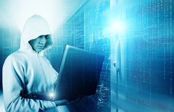 Hacker using laptop to steal identity against abstract glowing black background stock photography