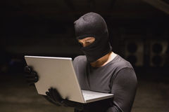Hacker using laptop to steal identity Stock Photography
