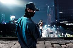 Hacker using mobile phone on the rooftop Stock Image