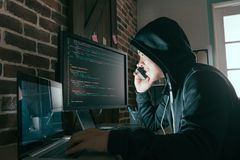 Hacker using mobile smartphone calling for victim. And stealing personal information through data in order to scamming ransom stock photography