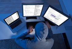 Hacker using multiple computers to steal data. Side view of hacker using multiple computers to steal data at table Royalty Free Stock Image