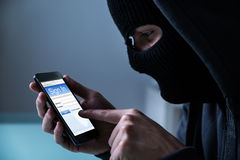 Free Hacker Using Smart Phone To Steal Data Royalty Free Stock Photo - 77510525