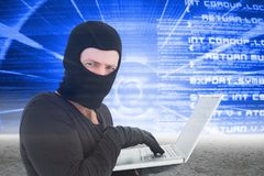 Hacker using a white laptop on blue interface Stock Photo