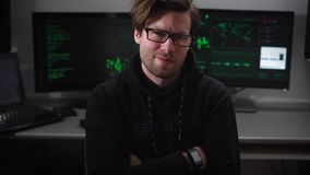 Hacker villain malicious eyes looking when the camera moves on him, against the background work computer monitors. IT stock video footage