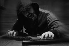 Hacker w kapiszonie siedzi i pracuje za komputerem obrazy royalty free