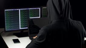 Hacker w kapiszonu łupania kodzie używać laptop i komputery od jego ciemnego hackera pokoju zbiory