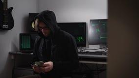 Hacker w komputerowym pokoju Mężczyzna w kurtce z kapiszonem, szkłami i pieniądze w rękach, siedzi w krześle Facet z zdjęcie wideo