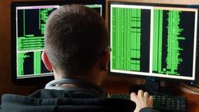 Hacker w szkłach łama kod Kryminalnego hackera sieci drążący system od jego ciemnego hackera pokoju Program komputerowy Zdjęcie Stock