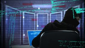 Hacker wearing a face mask. Rear view of a hacker wearing a face mask working on a laptop while interface codes are running around the foreground. The background stock video footage