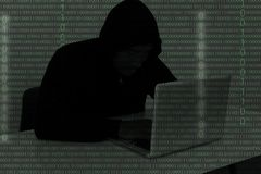 Hacker wearing a hooded top using laptop computer in the dark. T Royalty Free Stock Photography