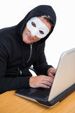 Hacker with white mask using laptop and looking at camera Royalty Free Stock Images