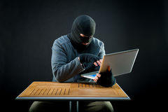 Hacker at work. On black background Royalty Free Stock Photography