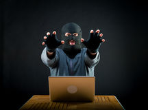 Hacker at work. Hacker stretching his arms forward, he'll come for your laptop Stock Images