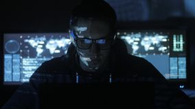 Male hacker programmer working at computer while blue code characters reflect on his face in cyber security center