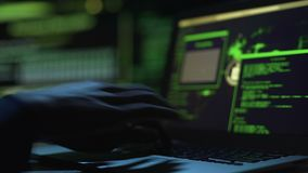 Hacker working on creating malicious software, actively typing on laptop keypad. Stock footage stock video footage